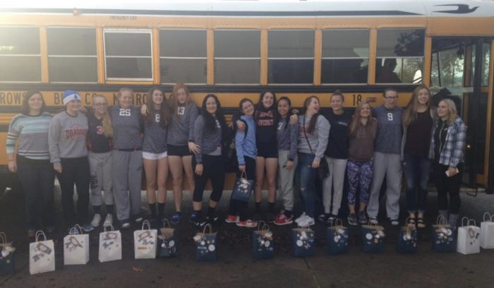 Team photo in front of school bus